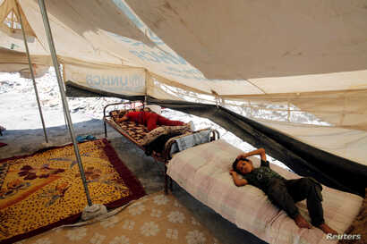 Children rest in a tent near their destroyed house in the old city of Mosul, Iraq, Aug. 22, 2018.