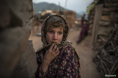 FILE - Soniya, 6, whose family moved to Islamabad from Pakistan's Khyber-Pakhtunkhwa province to look for work, stands outside their house on the outskirts of Islamabad.