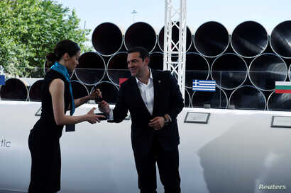 Greece's Prime Minister Alexis Tsipras prepares to sign during the Trans Adriatic Pipeline inauguration ceremony, in the northern Greek city of Thessaloniki, May 17, 2016.