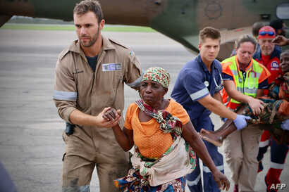 People are escorted to safety by aid workers at the airport of the coastal city of Beira in central Mozambique on March 19, 2019, after the area was hit by the Cyclone Idai.