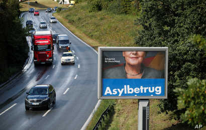 "FILE - A revolving election campaign poster of Germany's anti-immigration party, Alternative fuer Deutschland, AfD, reads ""Asylum fraud"" as Angela Merkel, German chancellor and leader of the Christian Democratic Union party, CDU, appears partly on a ..."
