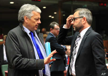 FILE - Belgium's Foreign Minister Didier Reynders, left, talks with Germany's Minister of State Michael Roth during an EU general affairs meeting, at the European Council building in Brussels, May 13, 2014.