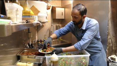 Refugee cook Abdell Baset prepares a Syrian dish for restaurant patrons in Brussels.