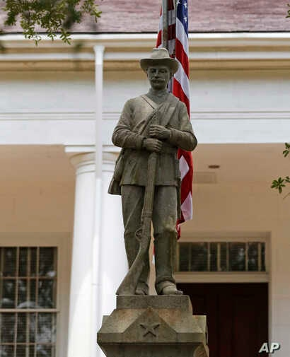 In this Wednesday, Aug. 1, 2018 photo, a statue commemorating fallen confederate soldiers stands on front of the East Feliciana Parish Courthouse in Clinton, La.