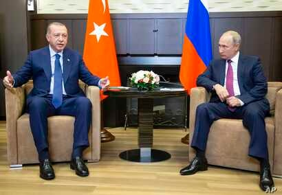 Turkish President Recep Tayyip Erdogan (L) speaks to Russian President Vladimir Putin, during their meeting in the Bocharov Ruchei residence in the Black Sea resort of Sochi in Sochi, Russia, Sept. 17, 2018.