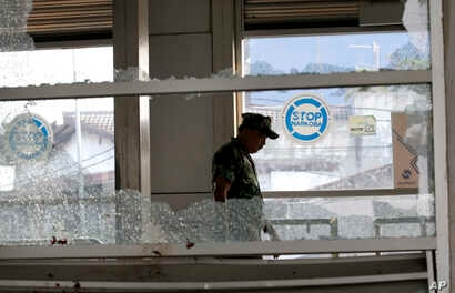 """A military officer inspects a bus stop damaged in Wednesday's suicide bombings in Jakarta, Indonesia, May 25, 2017. Indonesia's President Joko """"Jokowi"""" Widodo ordered a thorough investigation of the network behind two suicide bombings that targeted p..."""