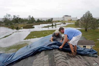 """Jeff Pyron, left, and Daniel Lilly cover Lilly's roof after Tropical Storm Florence hit Davis, N.C., Sept. 15, 2018. The town had 4½ feet of storm surge. """"I had my house raised for Irene cause I got flooded from the bottom. Now i'm getting flooded f..."""