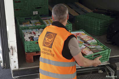 FILE – A volunteer loads a truck with food goods donated by a supermarket to charity organizations in l'Hay-les-Roses, France, May 26, 2015. France is cracking down on food waste with legislation banning big supermarkets from destroying unsold but ...