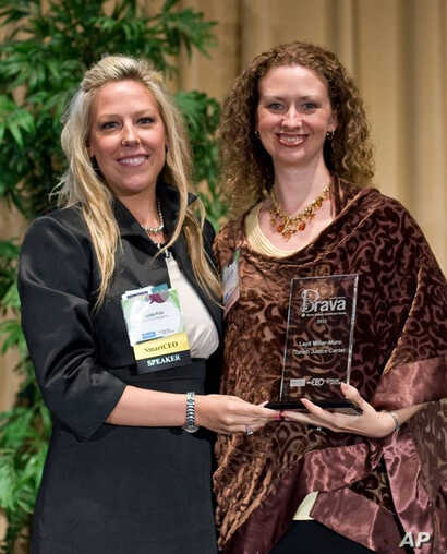Layli Miller-Muro, (right), executive director of the Tahirih Justice Center, receives a 2010 BRAVA! Women Business Achievement Award.