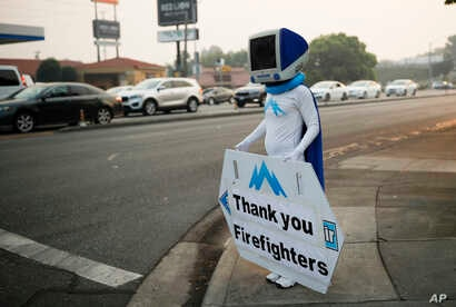 A man, who usually advertises a computer repair store, holds up a sign thanking firefighters working on the Carr Fire,  Aug. 13, 2018, in Redding, California.