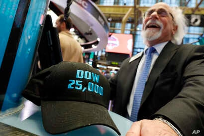 """FILE- Trader Peter Tuchman smiles as he poses with an old """"Dow 25,000"""" hat on the New York Stock Exchange trading floor, Jan. 30, 2019."""