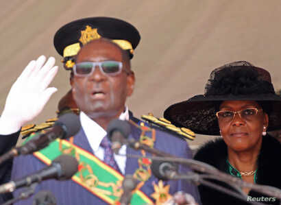 FILE - Zimbabwe President Robert Mugabe (L) and his wife Grace look on during the Defense Force's 36th Anniversary celebrations in the capital Harare, Zimbabwe, Aug. 9, 2016.