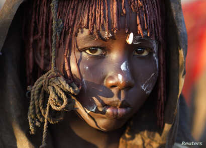 A Pokot girl, covered in animal skins, walks to a place where she will rest after being circumcised in a tribal ritual in a village about 80 kilometres from the town of Marigat in Baringo County, October 16, 2014. The traditional practice of circumci...