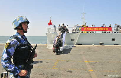 "FILE - A navy soldier (L) of People's Liberation Army (PLA) stands guard as Chinese citizens board the naval ship ""Linyi"" at a port in Aden."