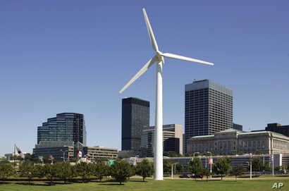 FILE - A small wind turbine rises in front of the downtown skyline at the Great Lakes Science Center in Cleveland.