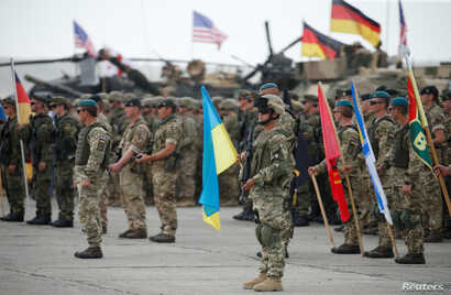 """Servicemen from different countries stand at attention during an opening ceremony of the NATO-led military exercises """"Noble Partner 2018"""" at Vaziani military base outside Tbilisi, Georgia, Aug. 1, 2018."""
