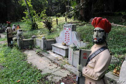 FILE - Statues of the sikh guards are seen standing by the side of a graveyard at Bukit Brown, one of Singapore's oldest cemeteries, Aug, 16, 2011.