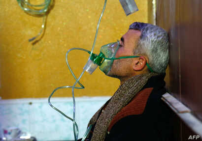 A Syrian man wears an oxygen mask at a makeshift hospital following a reported gas attack on the rebel-held besieged town of Douma in the eastern Ghouta region on the outskirts of the capital Damascus, Jan. 22, 2018.