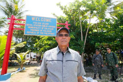 FILE - Philippine Defense Secretary Delfin Lorenzana tours the Philippine-claimed island of Pag-asa, also known as Thitu, during his visit to the Spratlys chain of islands in the disputed South China Sea, April 21, 2017.