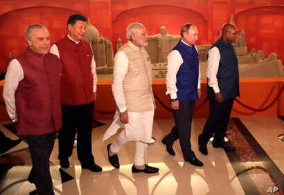 Leaders of BRICS nations, from left, Brazilian President Michel Temer, Chinese President Xi Jinping, Indian Prime Minister Narendra Modi, Russian President Vladimir Putin and South African President Jacob Zuma walk past sand sculptures at their summi...
