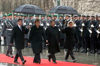 FILE - German Chancellor Angela Merkel, second left, welcomes the President of Egypt, Mohammed Morsi, second right, with military honors at the chancellery in Berlin, Germany, Wednesday, Jan. 30, 2013.