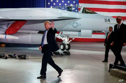 President Donald Trump waves as he walks off after participating in a roundtable discussion on tax policy at the Boeing Company, March 14, 2018, in St. Louis.