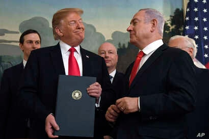 President Donald Trump smiles at Israeli Prime Minister Benjamin Netanyahu, right, after signing a proclamation in the Diplomatic Reception Room at the White House in Washington, Monday, March 25, 2019. Trump signed an official proclamation formally ...
