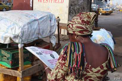 A woman reads the newspaper in Westfield, Banjul, Gambia, June 7, 2017. (S.Christensen/VOA)