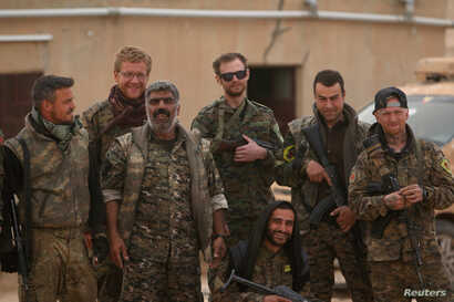 Syrian Democratic Forces (SDF) fighters pose with foreign volunteer fighters inside Tabqa military airport after taking control of it from Islamic State fighters, west of Raqqa city, Syria April 9, 2017.