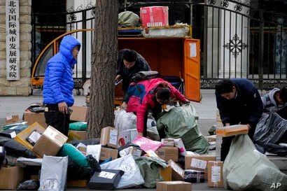 Delivery workers sort boxes of goods for their customers outside the capital city development academy in Beijing, China, Oct. 30, 2018.