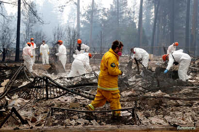 A volunteer search and rescue crew from Calaveras County comb through a home destroyed by the Camp Fire in Paradise, California, U.S., Nov. 13, 2018.