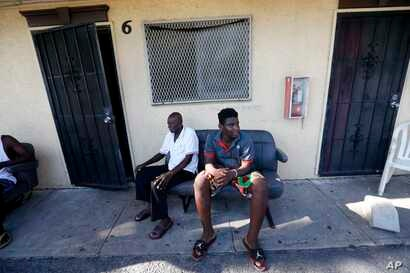 Woodchy Darius, right, sits outside the small cinderblock apartment he lives in, in the aftermath of Hurricane Irma, in Immokalee, Florida, Sept. 12, 2017.