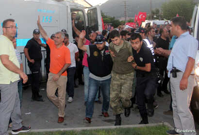 Soldiers suspected of being involved in the coup attempt are escorted by policemen as they arrive at a courthouse in the resort town of Marmaris, Turkey, July 17, 2016.