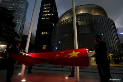 FILE - A Chinese national flag is lowered outside the Legislative Council, part  of a daily ceremony in Hong Kong, Nov. 7, 2016. The day before, China's parliament passed an interpretation of Hong Kong's Basic Law saying lawmakers must swear allegian...