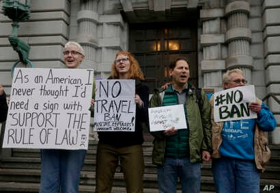 FILE -  Kay Aull, from left, holds a sign and chants with Beth Kohn, Paul Paz y Mino and Karen Shore outside of the 9th U.S. Circuit Court of Appeals in San Francisco, Calif.