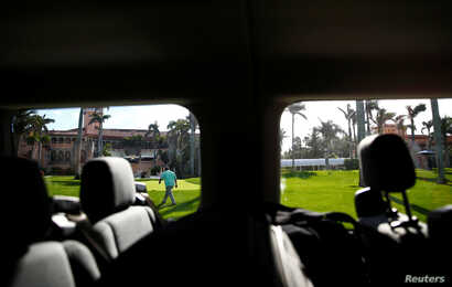 A United States Secret Service agent is seen from a press van at President Donald Trump's Mar-a-Lago estate in Palm Beach, Florida.