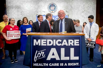 FILE - Sen. Bernie Sanders, I-Vt., is joined by Democratic Senators and supporters as he arrives for a news conference on Capitol Hill in Washington, Sept. 13, 2017.