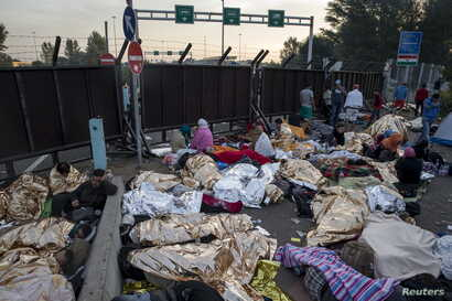 Migrants sleep on a highway in front of a barrier at the border with Hungary near the village of Horgos, Serbia, Sept. 16, 2015.