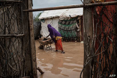 FILE - A woman cooks on a wheelbarrow beside flooded shelters after a heavy rainy season downpour at the Dadaab refugee complex, in the north-east of Kenya, on April 17, 2018.