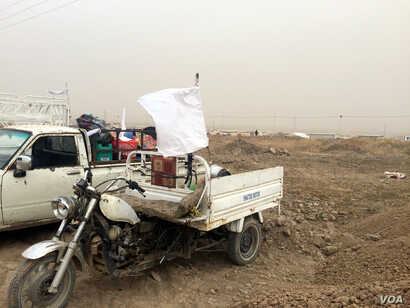 While many families flee on foot, those in their own cars hang white flags to indicate they are not with any military organization in Kurdish, Iraq, Nov. 1, 2016. (H. Murdock/VOA)