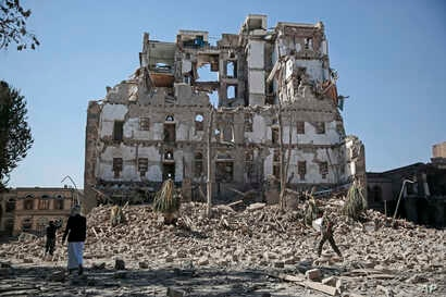 Houthi Shiite rebels walk amid the rubble of the Republican Palace that was destroyed by Saudi-led airstrikes, in Sanaa, Yemen, Dec. 6, 2017.