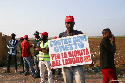 """An African migrant laborer holds a banner reading """"against all ghetto, for the dignity of work"""" during a march to protest against his work conditions in Italy, following the death of 16  colleagues in two separate road accidents, near Foggia, Italy, ..."""