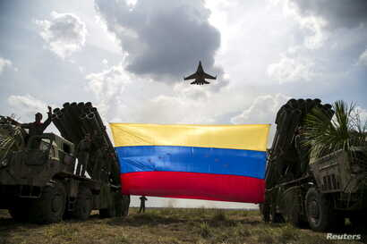 "A Russian-made Sukhoi Su-30MKV fighter jet of the Venezuelan Air Force flies over a Venezuelan flag tied to missile launchers, during the ""Escudo Soberano 2015"" (Sovereign Shield 2015) military exercise in San Carlos del Meta in the state of Apure Ap"