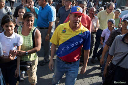 Venezuelan presidential candidate Henri Falcon walks during a campaign event at the slum of Catia in Caracas, April 2, 2018.