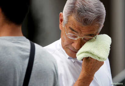 A businessman wipes his face while walking on a street during a heatwave in Tokyo, July 23, 2018.