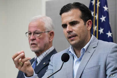 Flanked by Public Safety Secretary Hector Pesquera, Puerto Rico Gov. Ricardo Rossello speaks during a press conference regarding the aftermath of Hurricane Maria, in San Juan, Puerto Rico, Aug. 28, 2018.