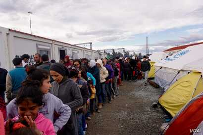 Refugees queue up for food; they can wait in line for three or four hours. (J. Dettmer/VOA)