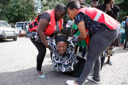 Kenya Red Cross personnel helps a woman reacting after learning of a family member killed during a recent terrorist attack Wednesday, Jan. 16 2019, at the Chiromo Mortuary, Nairobi, Kenya.