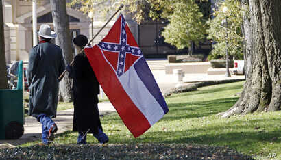 FILE -A couple leaves the grounds of the state Capitol in Jackson, Miss., after participating in a rally in support of keeping the Confederate battle emblem on the state flag, Jan. 19, 2016.