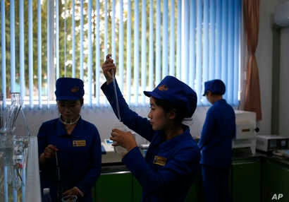 In this Oct. 22, 2018, photo, workers test samples of products for consistency at the factory lab at Songdowon General Foodstuffs Factory in Wonsan, North Korea.